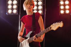 A woman playing electric guitar performing on stage Stock Photos
