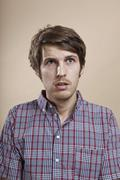 Portrait of a man looking confused, studio shot Stock Photos