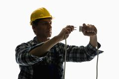 A construction worker putting a plug into an extension cord Stock Photos