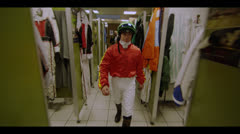 JOCKEY WALKS THROUGH DRESSING ROOM - stock footage