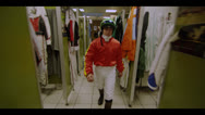 Stock Video Footage of JOCKEY WALKS THROUGH DRESSING ROOM