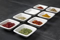 Various herbs and spices in small bowls Stock Photos