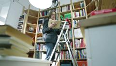 Man leafing a book near the bookcase 2 Stock Footage