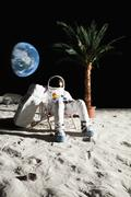 An astronaut on the moon relaxing in a beach chair Stock Photos