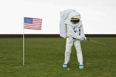 An astronaut swinging a golf club next to an American flag - stock photo
