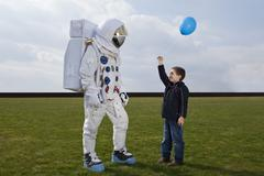 A boy holding out a balloon to an astronaut Stock Photos