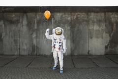 An astronaut on a city sidewalk holding a balloon Stock Photos