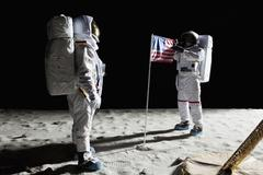 Two astronauts on the moon, an American flag in between them Stock Photos