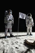 Two astronauts on the moon, a blank white flag in between them Stock Photos