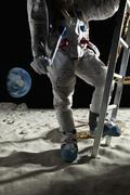 An astronaut climbing the ladder of a lunar lander on the moon Stock Photos