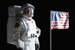 An astronaut with a serious expression standing next to an American flag - stock photo