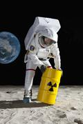 An astronaut rolling a drum of toxic material on the moon surface Stock Photos
