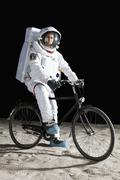 An astronaut on a bicycle on the moon - stock photo