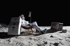 An astronaut on the moon watching television Stock Photos