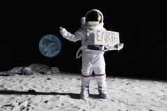 An astronaut on the moon with his thumb out, holding 'EARTH' sign Stock Photos