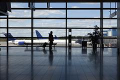 A businessman walking by a window of an airport, silhouette Stock Photos