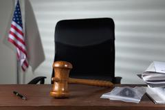A gavel on a judge's desk in an empty courtroom Stock Photos