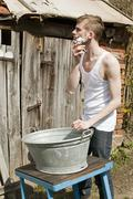 A rustic man shaving outdoors - stock photo