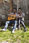 Stock Photo of A man playing an acoustic guitar with his girlfriend