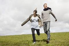 A couple running down a hill while holding hands Stock Photos