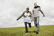 Stock Photo of A couple running down a hill while holding hands