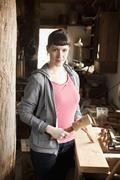 A woman in a workshop holding a chisel and mallet Stock Photos