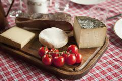 Cheese, tomatoes and cured ham on a wood cutting board Stock Photos