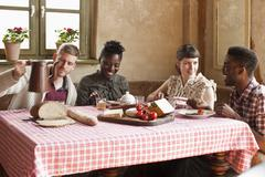 Two couples enjoying a simple rustic meal - stock photo