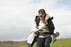 A young man catching his girlfriend after chasing her Stock Photos