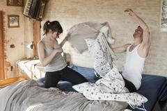 A boyfriend and his girlfriend having a pillow fight in bed Stock Photos
