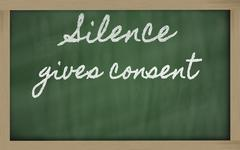 expression -  silence gives consent - written on a school blackboard with cha - stock photo