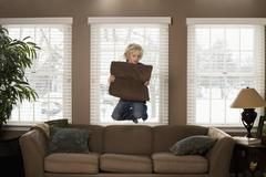 A boy holding a pillow and jumping in mid-air Stock Photos