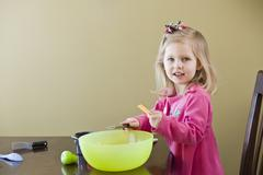 A girl playing with toy food and cooking utensils - stock photo