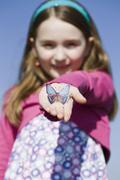 A girl holding a plastic butterfly in her hand Stock Photos