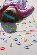A girl lying down behind felt alphabet letters - stock photo