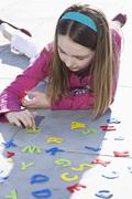 A girl playing with felt alphabet letters Stock Photos