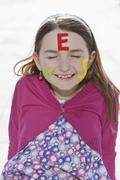 A girl with felt letters spelling YES on her face - stock photo
