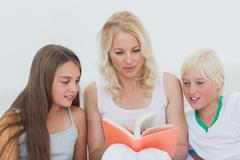 Mother reading a story to her children - stock photo