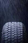 Detail of rain falling on a car tire - stock photo