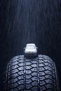 Detail of rain falling on a toy car on a tire - stock photo