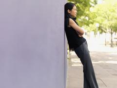 A businesswoman leaning against a wall Stock Photos