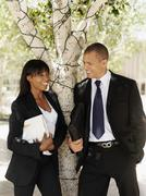 A businesswoman and businessman leaning against a tree and talking Stock Photos