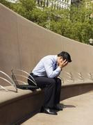 A distraught businessman with his head in hands - stock photo
