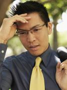 A businessman holding his forehead and grimacing - stock photo