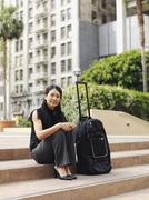 Stock Photo of A businesswoman sitting on a step next to a rolling suitcase