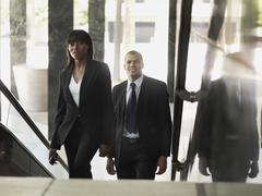 A businesswoman and businessman walking up stairs in an office building - stock photo