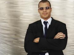 Portrait of a businessman with his arms crossed, wearing sunglasses - stock photo