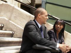 Stock Photo of A businessman and businesswoman sitting on some stairs and having a discussion