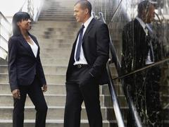 A businesswoman talking with a businessman outside of an office building Stock Photos