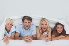 Cheerful family hiding under the blanket - stock photo